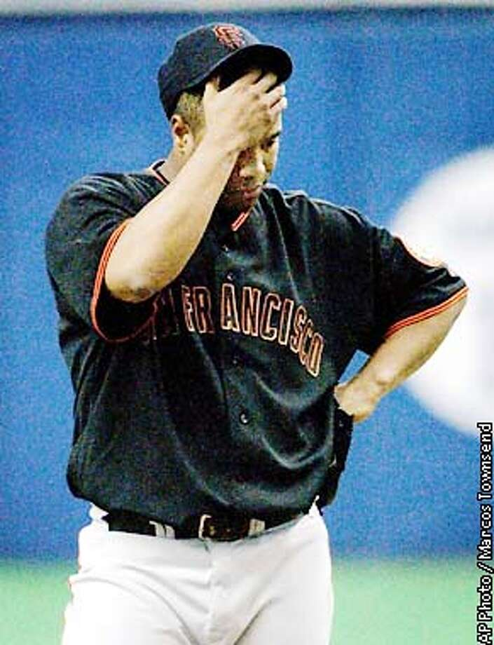 San Francisco Giants pitcher Livan Hernandez wipes his brow while pitching against Montreal Expos' Orlando Cabrera during third inning NL action May 10, 2002 in Montreal. Hernandez gave up four runs during the inning. (AP Photo/Marcos Townsend) Photo: MARCOS TOWNSEND