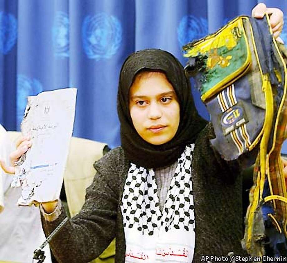 Palestinian Reem Hassan holds up a school book and a book bag that belonged to a Palestinian child that was killed by an Israeli landmine explosion, at a news conference, Friday, May 10, 2002, during the U.N. Children's summit at U.N. headquarters in New York. (AP Photo/Stephen Chernin) Photo: STEPHEN CHERNIN