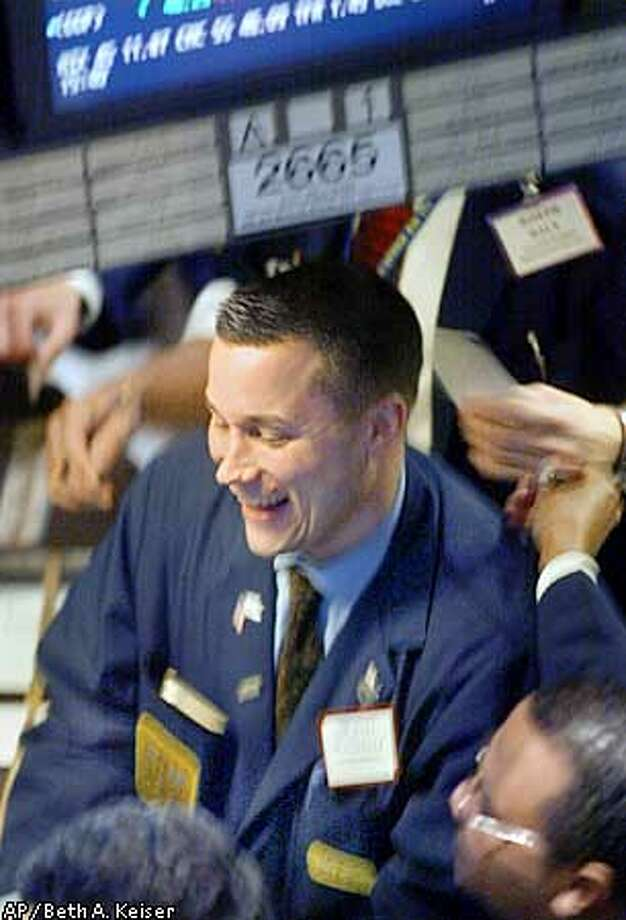 A trader smiles as the closing bell nears Wednesday, May 8, 2002, at the New York Stock Exchange in New York. The Dow Jones closed up 305.28, or 3.1 percent, at 10,141.83. (AP Photo/Beth A. Keiser) Photo: BETH A. KEISER