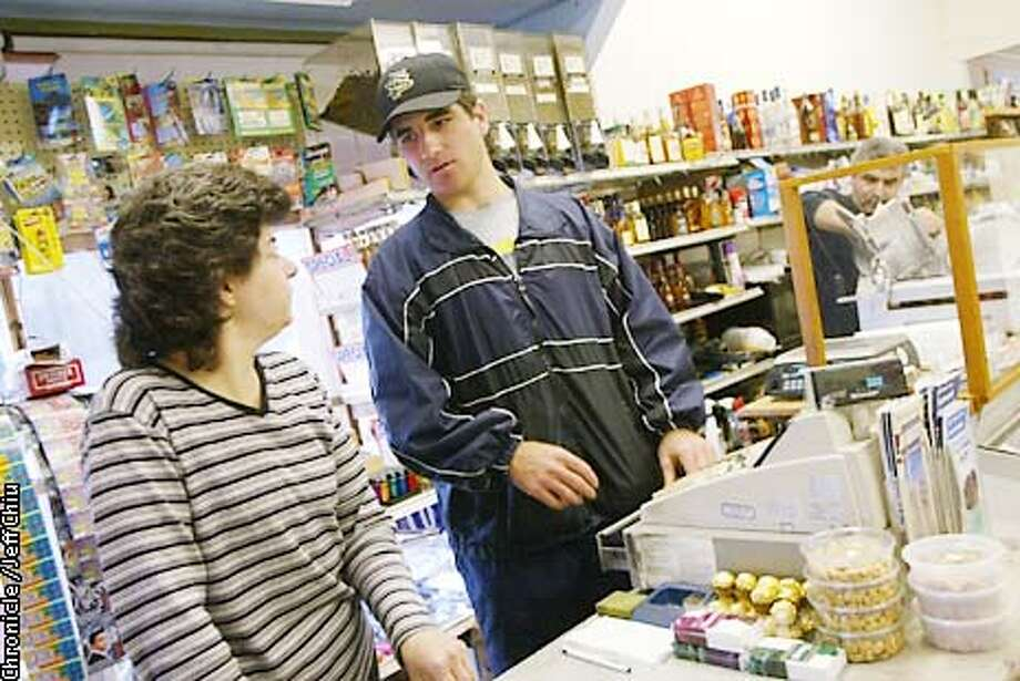 Khamis Zananiri, center, talks with his mother Nahla while working behind the counter, as his father Mufid, right, cleans up at their store, Golden State Market, on Friday evening in San Francisco hours after the USF baseball team lost to Loyola. Zananiri, a walk-on freshman third baseman at USF, is a former all-city player at Balboa high in SF, and sold hot dogs out of the snack stand during the first 45 games. Photo by Jeff Chiu/The Chronicle Photo: Jeff Chiu
