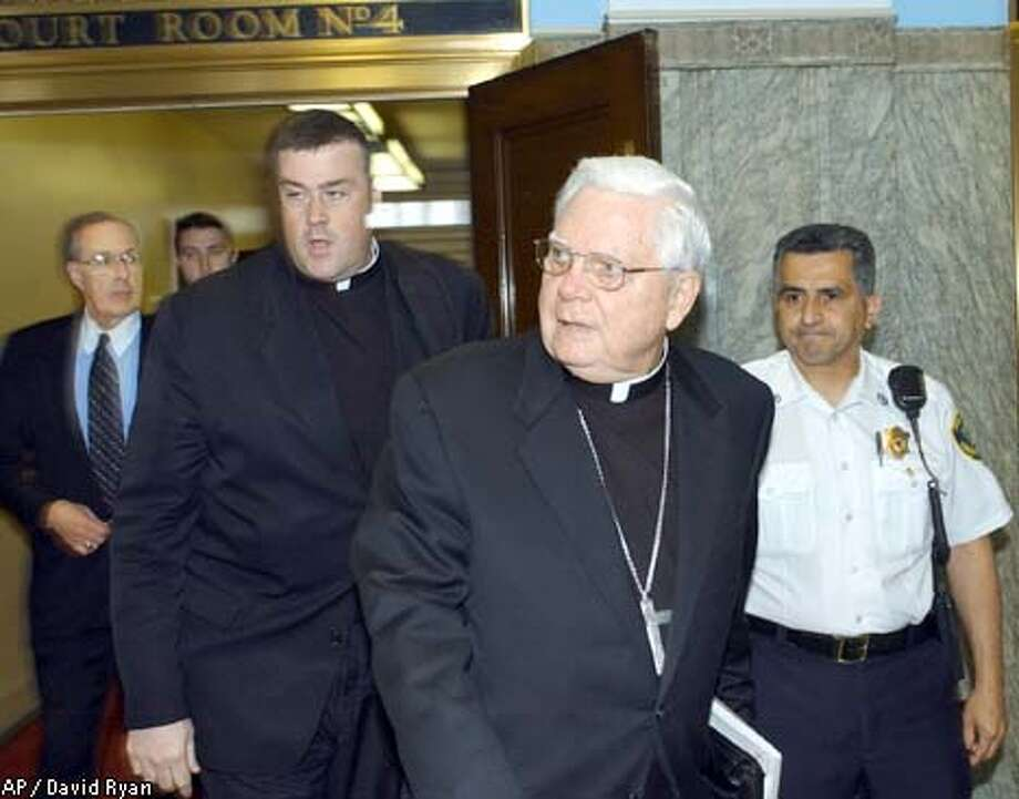 Cardinal Bernard Law (front) leaves Suffolk Superior Court in Boston after giving his first deposition in the clergy sex abuse scandal. Associated Press photo by David Ryan