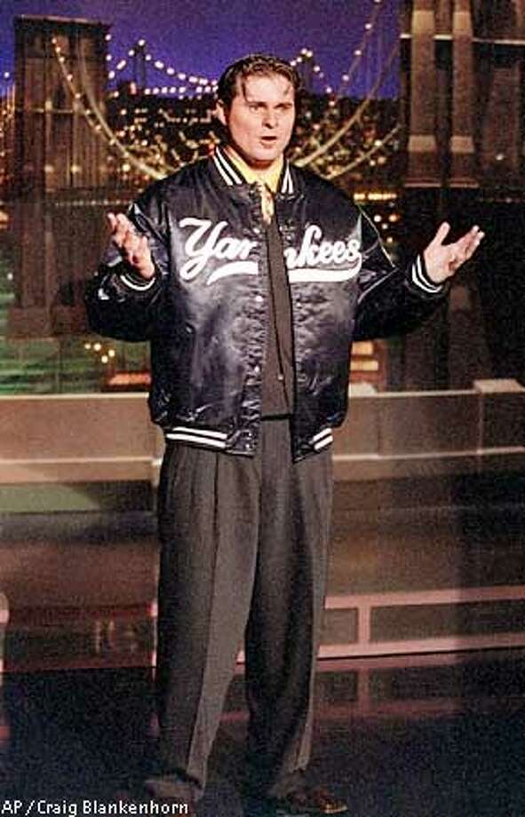 "Jason Giambi, who just signed a $120 million, seven-year deal to play baseball with the New York Yankees, reads the Top Ten List on the set of ""The Late Show With David Letterman"" in New York, Thursday, Dec. 13, 2001. (AP Photo/CBS, Craig Blankenhorn) Photo: CRAIG BLANKENHORN"