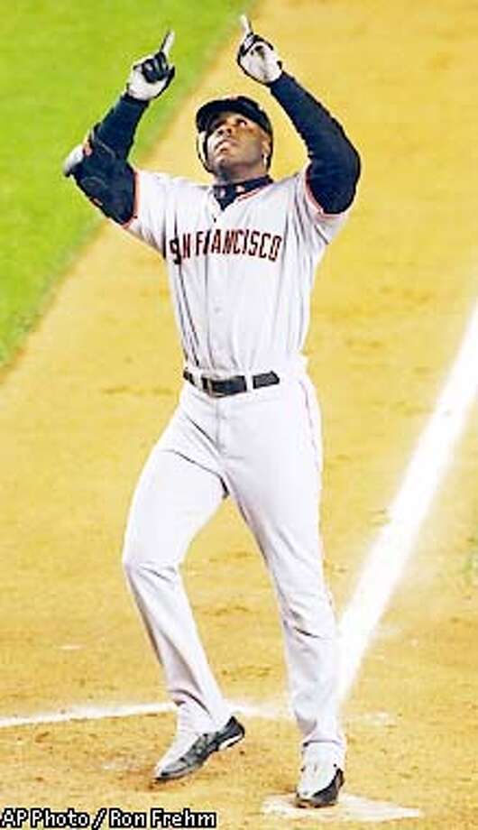 San Francisco Giants' Barry Bonds points to the sky as he steps on the plate after his solo home run in the fourth inning against the New York Mets, Thursday, May 9, 2002 at Shea Stadium in New York. (AP Photo/Ron Frehm) Photo: RON FREHM