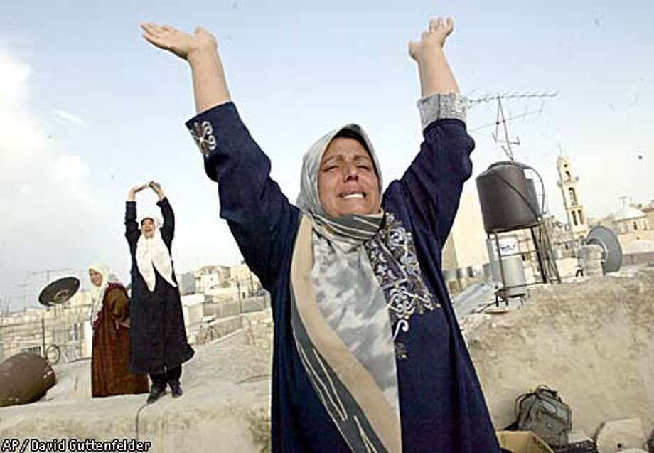 The sister of one of the 13 Palestinian militants taken from the Church of the Nativity waves and cries out from a Bethlehem rooftop. Associated Press photo by David Guttenfelder
