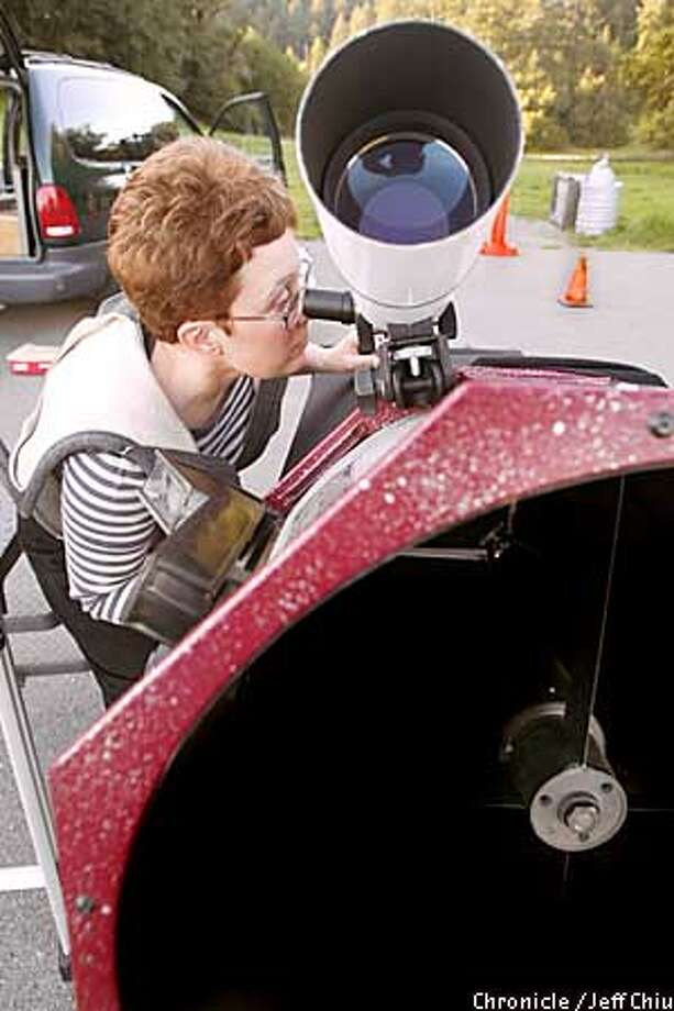Jane Houston Jones, president of the Astronomical Association of Northern California, sets up a telescope for a Mount Tam star party. Chronicle photo by Jeff Chiu