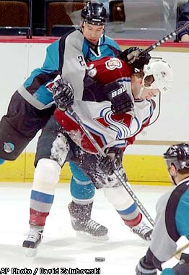 San Jose Sharks defenseman Mike Rathje, left, knocks off the helmet of Colorado Avalanche left winger Eric Messier as they battle for control of the puck near the Sharks' net in the first period Friday, Dec. 14, 2001, in Denver. (AP Photo/David Zalubowski) Photo: DAVID ZALUBOWSKI