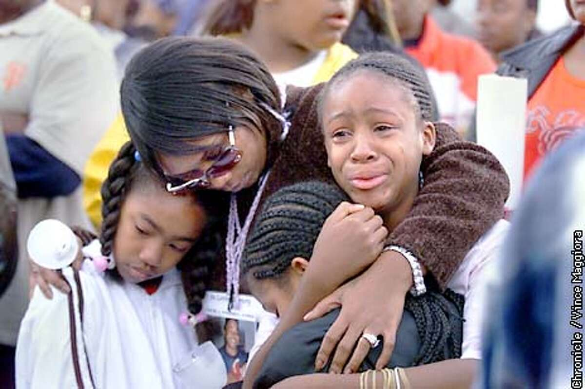 MARCH-C-25AUG01-MT-VM Jacalyn Pitcher with her hand on her face putting a candle down on 3 rd st. in hunters point for son Starvel Junious who was killed on may 3 2000 mothers and family march for murders of young black men. by Vince Maggiora