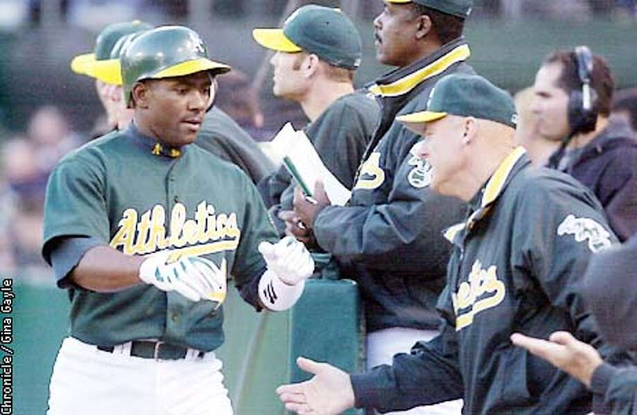 Miguel tejada is welcomed back to the dugout by Art Howe after a run in by (check who) in the second inning against Boston. Photo by Gina Gayle/The SF Chronicle. Photo: GINA GAYLE
