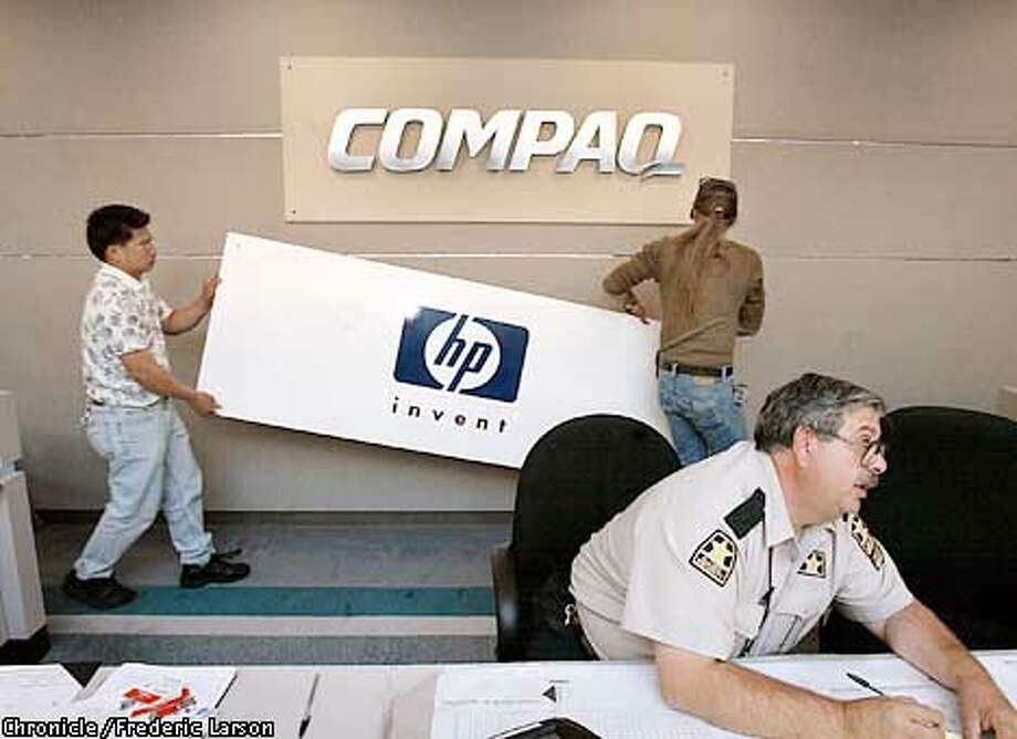 : Marc Juliano and Irmin Ronquillo (left) change the sign from Compaq to HP in the first day of the takeover. Chronicle photo by Frederic Larson Photo: FREDERIC LARSON