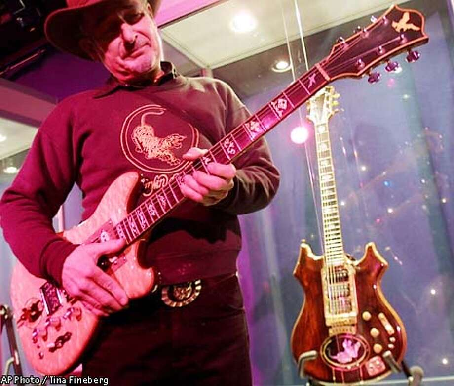 "Guitar maker Doug Irwin strums ""Wolf"" an electric guitar he custom made for the late Jerry Garcia, at Studio 54 Tuesday, May 7, 2002 in New York. The guitar is among 182 collectibles from the Grateful Dead and Jerry Garcia that will be auctioned by Guernsey's Wednesday, May 8, 2002. (AP Photo/Tina Fineberg) Photo: TINA FINEBERG"