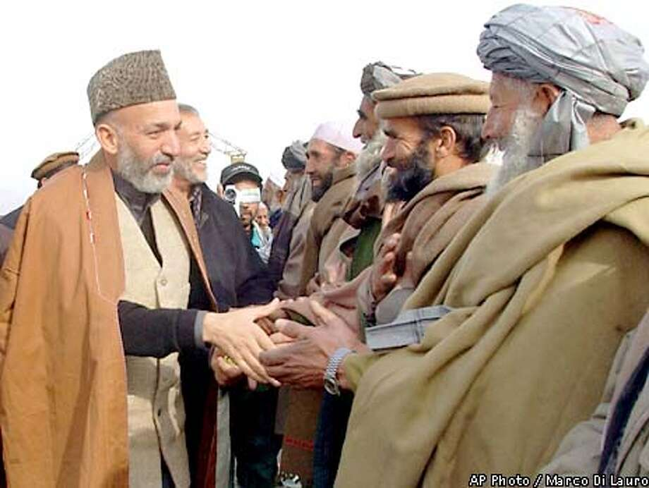 Hamid Karzai, left, interim prime minister of the Islamic Republic of Afghanistan, who will take power next Dec. 22, greets Afghans on the road from Kabul to Jebal Saraj, on his way to pray at the grave of slain opposition leader Ahmad Shah Massood in Bazarak district, 120 km (74 miles) north of the Afghan capital on Friday, Dec. 14, 2001. (AP Photo/Marco Di Lauro) Photo: MARCO DI LAURO