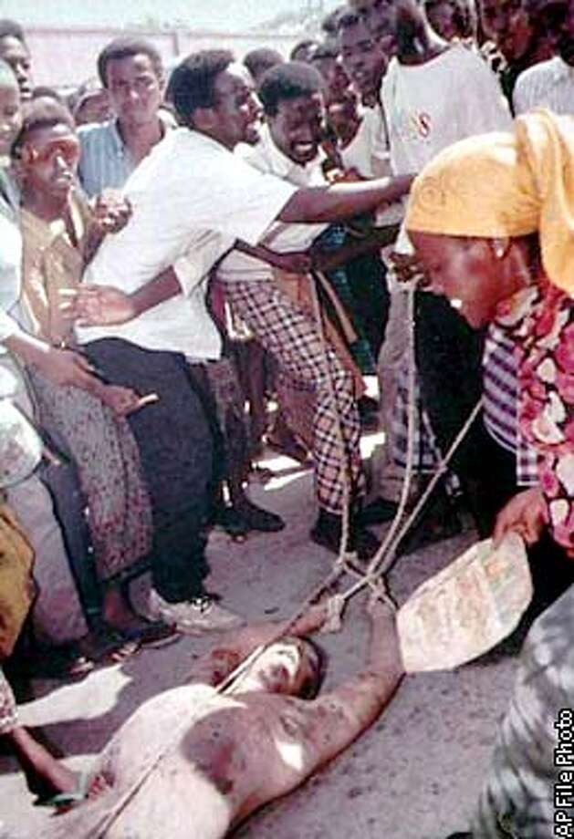 The body of a U.S. military airman is dragged with ropes through the dusty streets of war-torn Mogadishu, Somalia, Monday, Oct. 4, 1993. The dead soldier was one of five Americans killed Sunday during the first day of a major U.N. assault on warlord Mohamed Farah Aidid's military command. (AP photo/Toronto Star/Paul Watson)