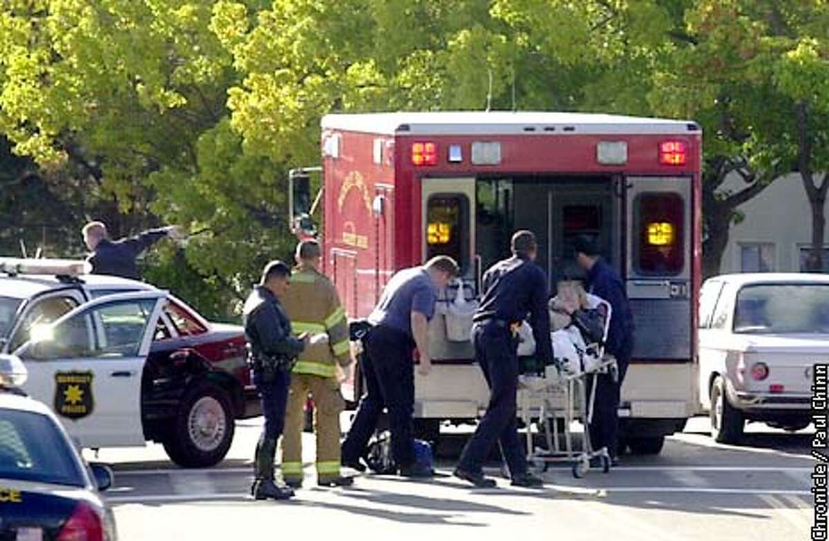 Paramedics wheeled the victim into an ambulance. The pedestrian was injured in an accident at Claremont Blvd. and Russell St. where the city has installed the new orange flag-waving system. PAUL CHINN/S.F. CHRONICLE