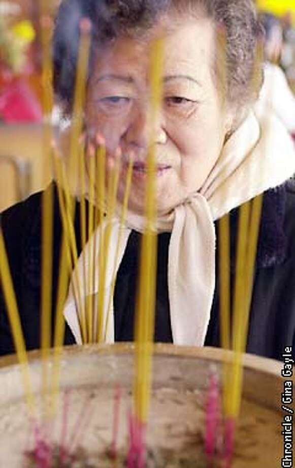 Mildred Fong, 84 one of the original ladies who helped create the original Taosist temple in Chinatown lights incense for offereings in the original temple. Photo by Gina Gayle/The SF Chronicle. Photo: GINA GAYLE