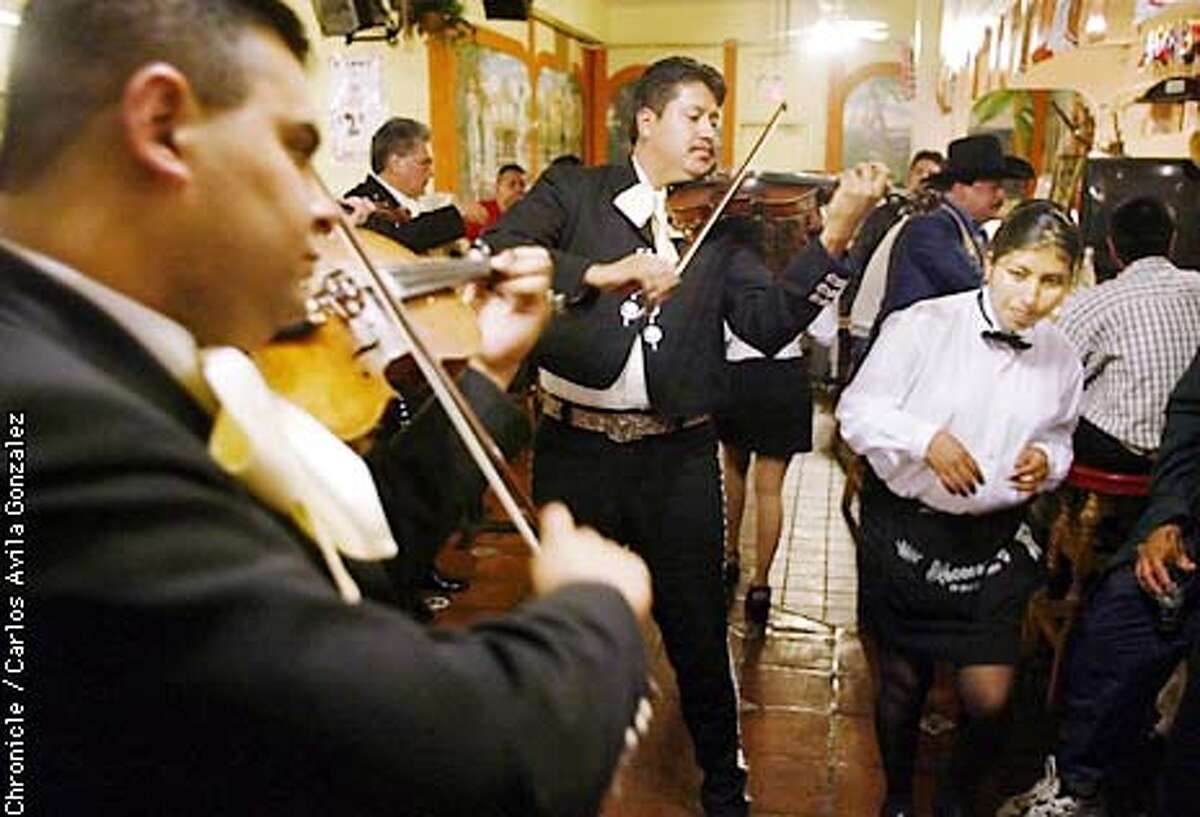 Mariachi Azteca's Abigail Torres (yes, Abigail, cq) left, and Oscar Rosales, center, play at the bar at Tacos Al Carbon as a waitress slips by in San Jose on Saturday, April 20, 2002. The Mariachi culture in the Bay Area is alive and well and thriving as many schools and community groups are starting classes and showcases for the art. (PHOTO BY CARLOS AVILA GONZALEZ/THE SAN FRANCISCO CHRONICLE)