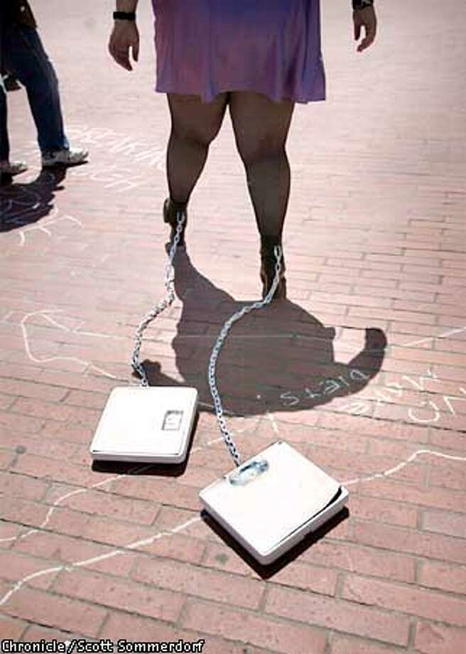 "Amanda Piaseki walked around Justin Herman Plaza with bathroom scales chained to her ankles to dramatize the obsession to dieting and the ""perfect body."" She also wore a photo of herself when she weighed 105 lbs, and was bulemic and anorexic. She was one of many activists to attend the ""Fat Freedom Fighter's NO-DIET DAY"" at Justin Herman Plaza. (SF CHRONICLE PHOTO BY SCOTT SOMMERDORF) Photo: SCOTT SOMMERDORF"