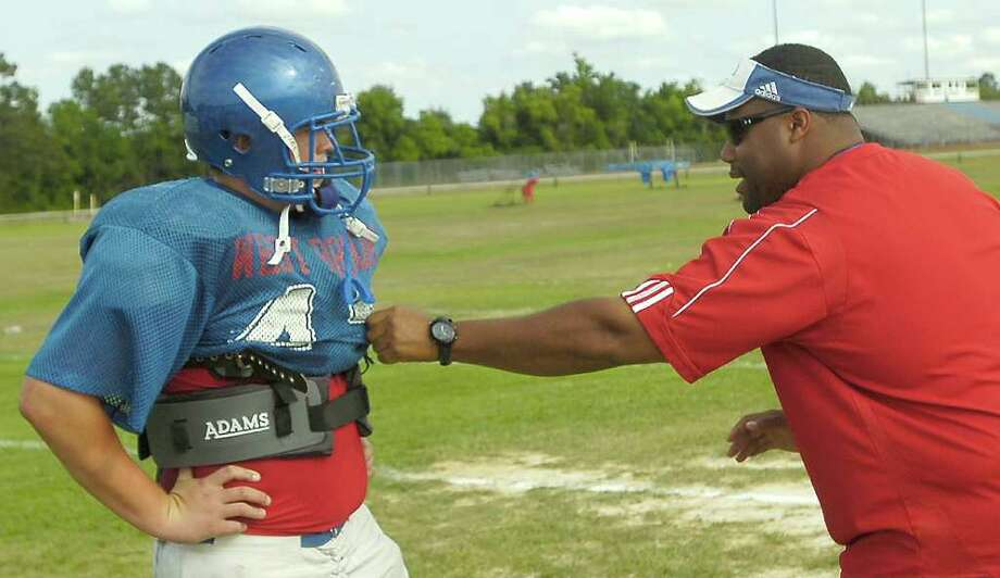 Spring football practice was held at the West Brook High School practice field Wednesday afternoon.  The team practiced many running plays.  Coach Joe Bowser, right, Offensive Line Coach, gives some pointers to one of his players after a drill that he did not like.    Dave Ryan/The Enterprise Photo: Tammy McKinley
