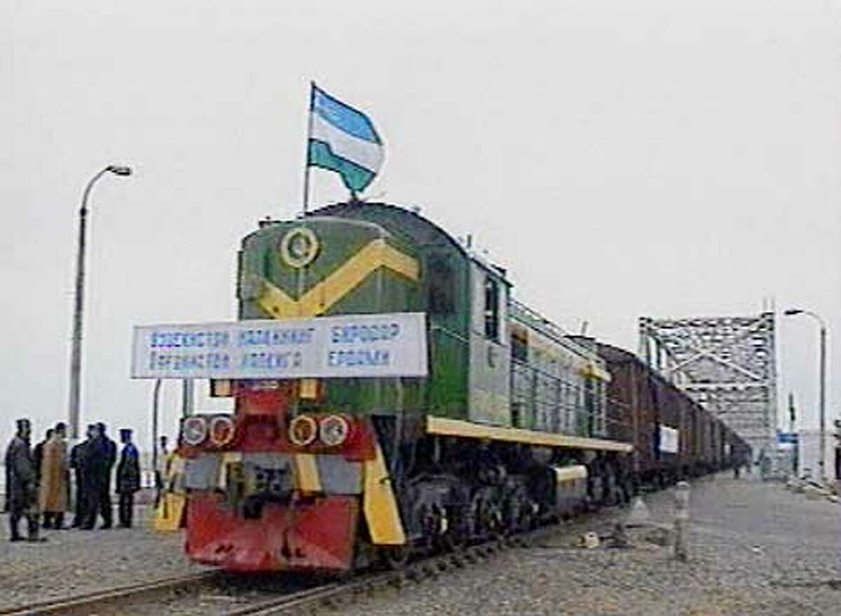 """The train carrying humanitarian aid from Uzbekistan to Afghanistan crosses the Friendship Bridge, which reopened today, in Hairaton, Afghanistan in this image taken from television Sunday, Dec. 9, 2001. The only bridge connecting Uzbekistan and Afghanistan reopened Sunday for the first time since 1997, and the first train carrying much-needed humanitarian aid for Afghanistan crossed over. The banner that adorns the front of the train reads """"from the Uzbek people to the Afghan people."""" The flag on the train is the Uzbek flag. (AP Photo/APTN) TV OUT"""