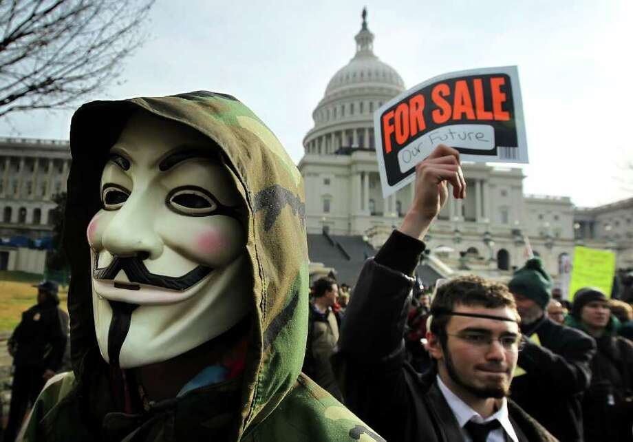 "A demonstrator wears a Guy Fawkes mask during an ""Occupy Congress"" rally at the West Front Lawn of the Capitol Jan. 17, 2012 in Washington, D.C. A driver delivering Chinese food in Stamford Friday night was robbed by a man wearing a Guy Fawkes mask. (Photo by Alex Wong/Getty Images) Photo: Alex Wong, Getty Images / 2012 Getty Images"