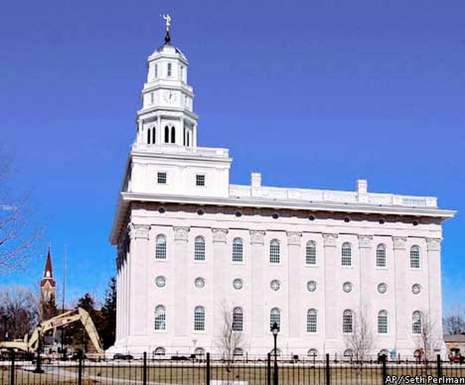 ADVANCE FOR SUNDAY MARCH 10--Sunlight reflects from the high limestone walls of the 65,000-square-foot temple and a spire reaches 161 feet, 9 inches into the sky. as the exterior is, as near as possible, an exact duplicate of the original Wednesday, Feb. 27, 2002, in Nauvoo, Ill. The Church of Jesus Christ of Later-day Saints in 1999 announced the would be rebuilt. More than 250,000 are expected to visit the community of 1,200 in May and June, when an open house will be heldbefore the temple is closed to non-Mormons. (AP Photo/Seth Perlman) Photo: SETH PERLMAN