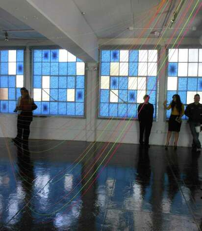 Strips of  blue painter's tape turn windows at Artpace into works of art.