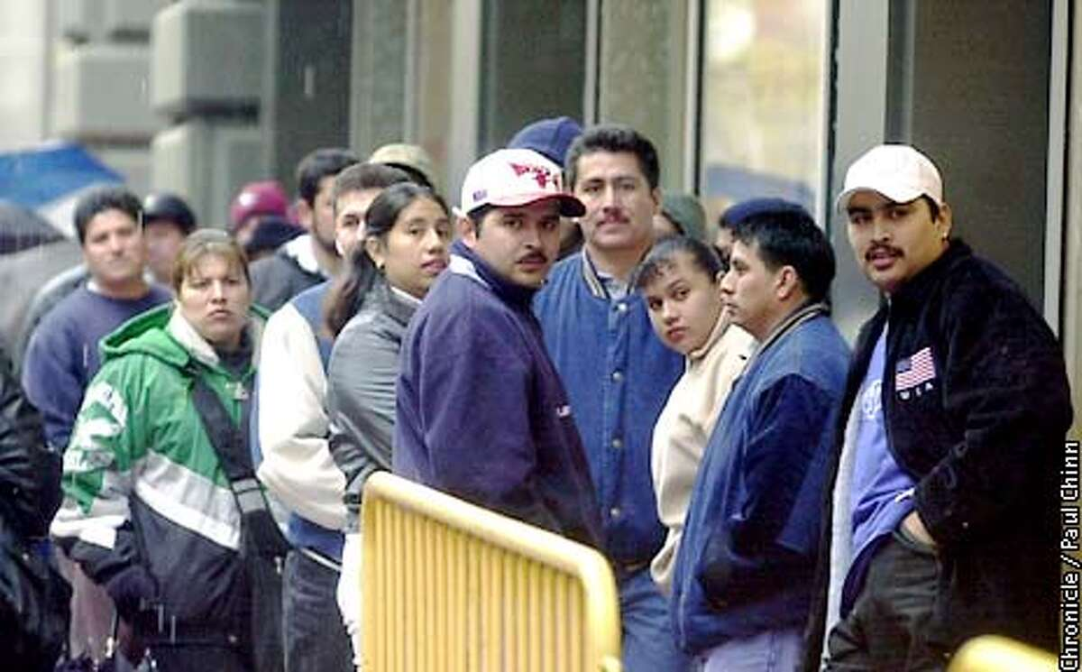 People braved the rain while waiting in a long line to apply for an ID card from the Mexican Consulate at the Flood Building. PAUL CHINN/S.F. CHRONICLE