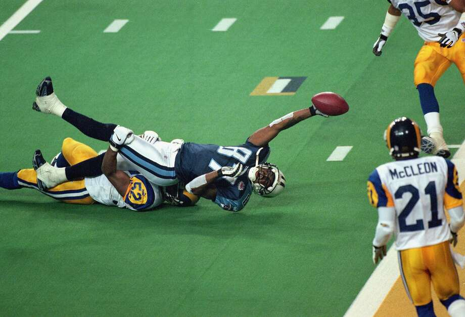 Kevin Dyson, with the Rams' Mike Jones clinging to him, stretches for the end zone on the final play of Super Bowl XXXIV. Photo: Tom Hauck