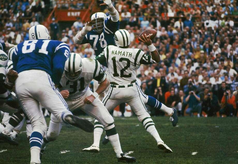 Jets quarterback Joe Namath passes despite the efforts of the Colts' Bubba Smith in Super Bowl III at the Orange Bowl in Miami. Photo: AP
