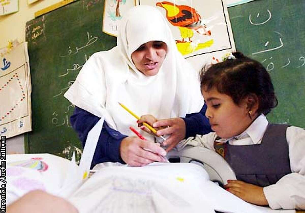 Kindergarten teacher Samira Ali El Hassain helps a student at a school operated by the Al Mujamma Al Islami in Gaza City on Saturday April 20, 2002. Photo By Justin Sullivan/For the Chronicle