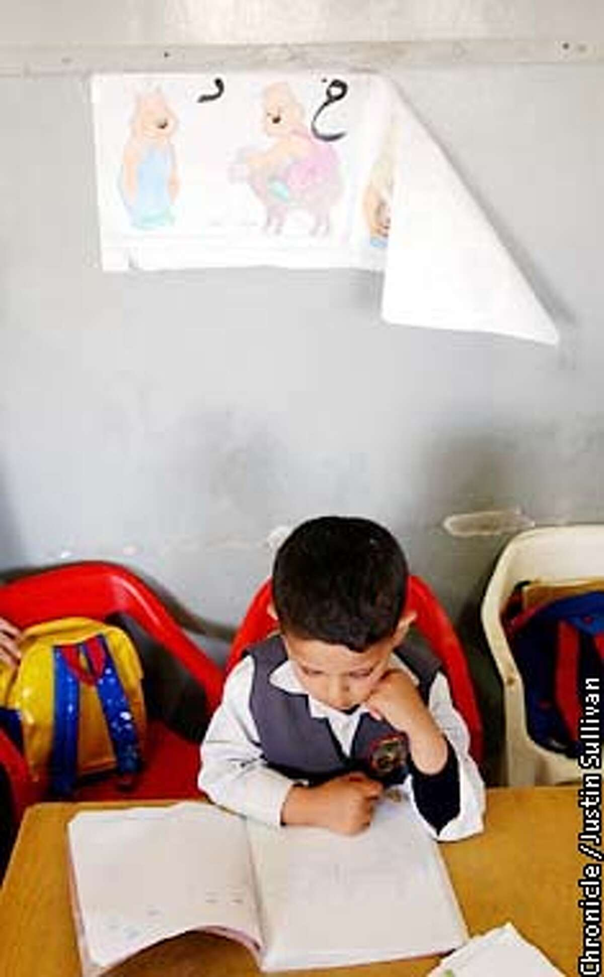 A Palestinian kindergarten student studies his coloring book at a school operated by the Al Mujamma Al Islami in Gaza City on Saturday April 20, 2002. Photo By Justin Sullivan/For the Chronicle