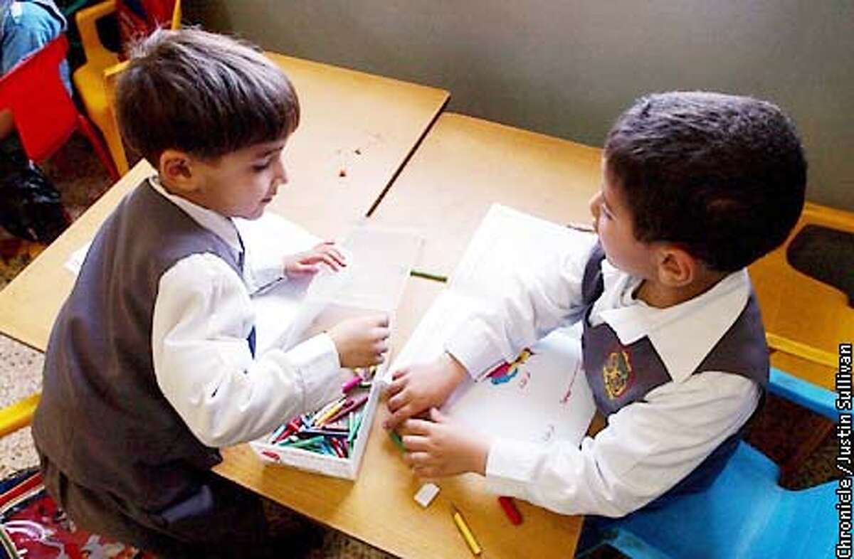 Two Palestinian kindergarten students play with crayons at a school operated by the Al Mujamma Al Islami in Gaza City on Saturday April 20, 2002. Photo By Justin Sullivan/For the Chronicle