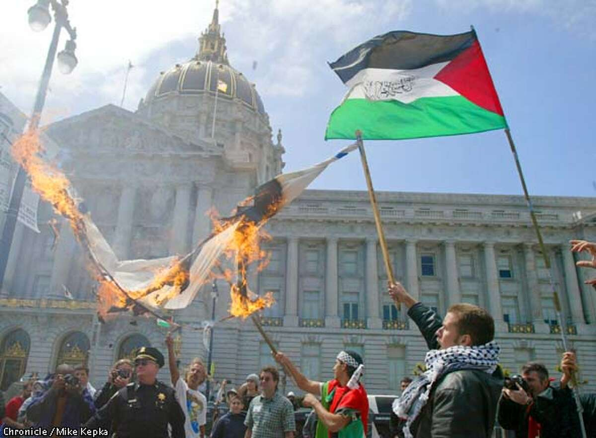 In protest of the Israeli occupation in Palestine, Mohammed Abdo, 18 of San Jose, and Omar Ata, 19, of Santa Clara (far right) and a group of other young Palestinian supporters burn an Israeli flag in front of San Francisco City Hall Saturday. BY MIKE KEPKA/THE CHRONICLE