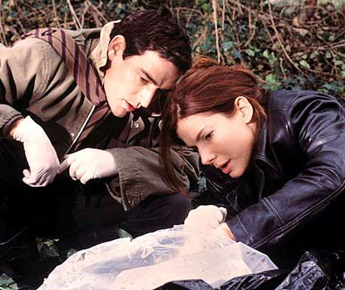 Cassie (Sandra Bullock) and her partner (Ben Chaplin) investigate a crime scene in the thriller
