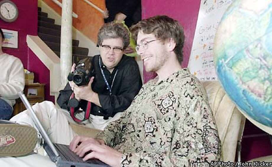 "Ken Anderson, center, an anthropologist with Intel, uses a video camera to document wireless online use by Greg Haines at the Hawthorne Youth Hostel, Thursday, April 11 2002, in SE Portland, Ore. Anderson said that Intel chose the Youth Hostel because it is a transient group of young and elderly travelers both domestic and international. ""They are the non-road warrior wireless user's"", Anderson say's, ""Different than the Marriot Crowd."" Intel donated a WiFi wireless access point to the hostel in order to conduct the study. (AP Photo/ John Klicker)"
