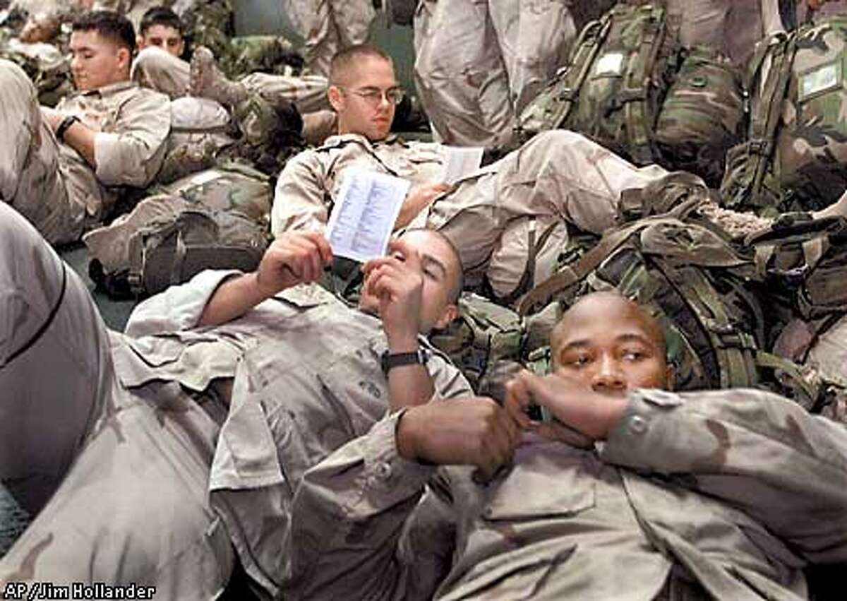 """EDS NOTE: PICTURE MAY HAVE BEEN REVIEWED AS IT WAS SENT VIA NAVY COMMUNICATIONS--U.S. Marines relax against their full battle gear as they review a list of English words translated into Farsi issued to them Sunday, Nov. 25, 2001, on the amphibious assault ship USS Peleliu somewhere in the northern Arabian Sea before the launch of the assault against a secret airstrip in southern Afghanistan. The list included phrases such as """"Lie down on your stomach!"""", """"We are Americans"""", and """"We are here to help."""" (AP Photo/Jim Hollander, pool)"""