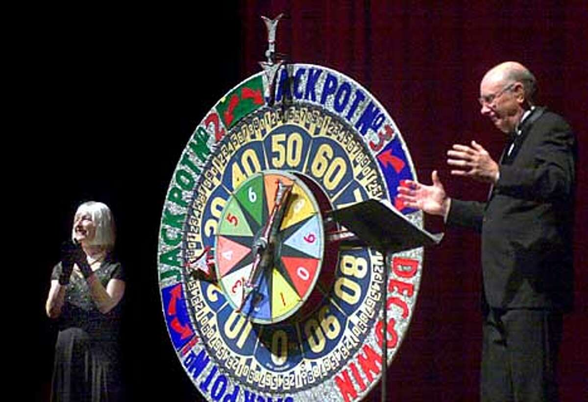 """Classic Movie Night at the Paramount Theatre in Oakland finds """"Dec-O Dotty"""" (Barbara Beggs) and Ken Walters working the """"Dec-O-Wheel."""" Chronicle photo by Christina Koci Hernandez"""