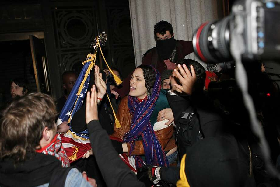 A woman pleads with Occupy Oakland protestors to not burn an American flag found inside Oakland City Hall during an Occupy Oakland protest, Saturday, January 28, 2012, in Oakland, Calif. Police were in the process of arresting about 100 Occupy protesters for failing to disperse Saturday night, hours after officers used tear gas on a rowdy group of demonstrators who threw rocks and flares at them and tore down fences.  (AP Photo/Beck Diefenbach) Photo: Beck Diefenbach, Associated Press