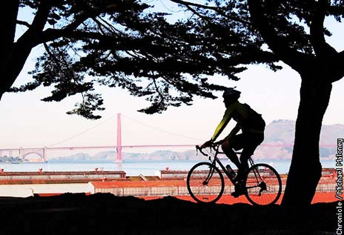 ROUNDSF1-C-28FEB02-OT-MJM Reporter Carl Hall rides above the bright red roofs of Fort Mason near the Marina Green. A bike ride around the perimeter of SF allows you to take in all the various neighborhoods at a leisurely pace. CHRONICLE PHOTO BY MICHAEL MALONEY