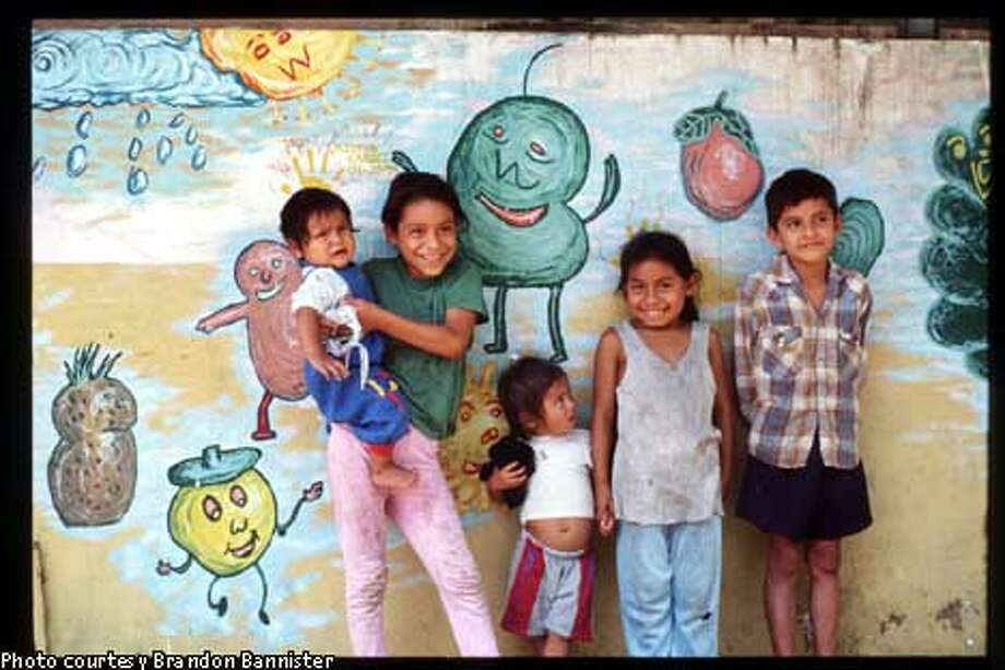 Ecuadoran children stand in front of one of the murals created by Brandon Bannister during his four-year stint in the Peace Corps. Photo courtesy of Brandon Bannister