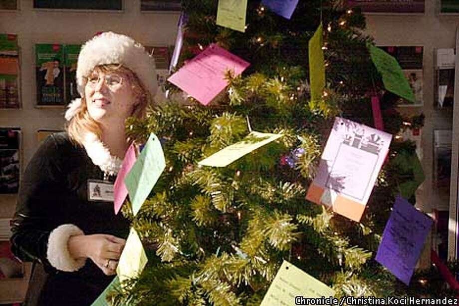 "PNHERO23cd-C-15NOV01-PF-CKH  CHRISTINA KOCI HERNANDEZ/CHRONICLE  Jennifer hangs wishes for gifts on the wells Fargo tree in Milpitas.Jennifer Cullenbine, founder of the ""Family Giving Tree,"" an organization that collects gifts for local families in need and the homeless. Photo: CHRISTINA KOCI HERNANDEZ"
