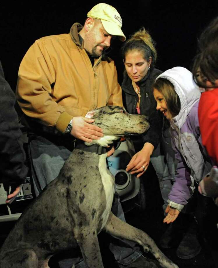 From left, Wilson and Renee Diaz and their five-year-old daughter Bridget welcome back their dog Eyore as he is returned to them after being missing Monday, Jan. 30, 2012 in Rensselaer, N.Y. The Great Dane was found tied to a tree by Schenectady County Community College.  (Lori Van Buren / Times Union) Photo: Lori Van Buren