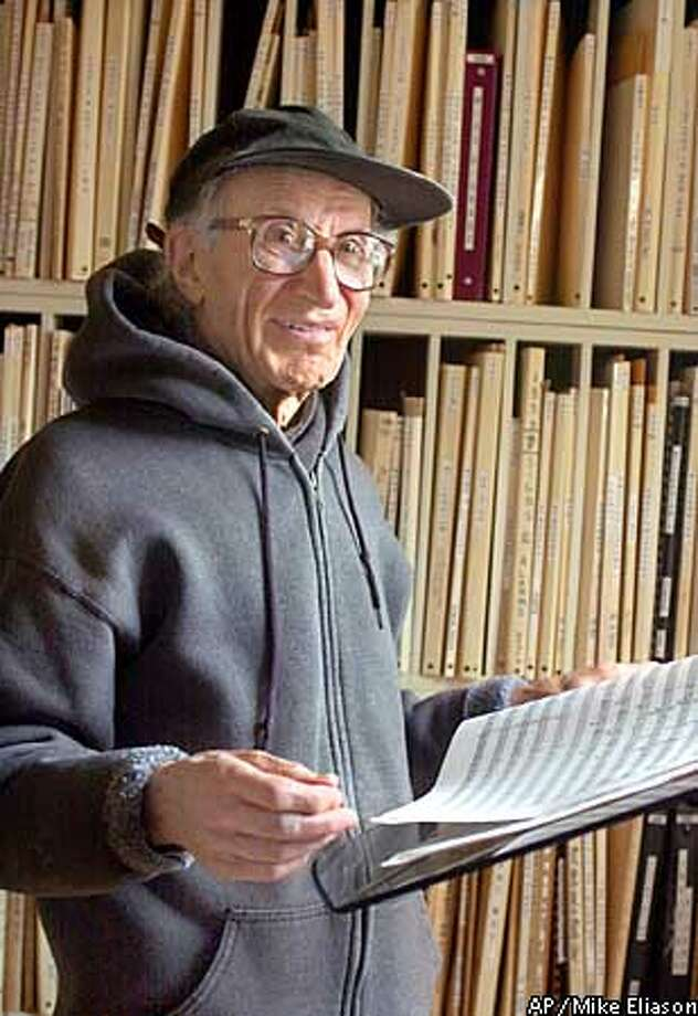 "Pulitzer Prize winner for music, Henry Brant, 88, looks over his winning work, ""Ice Field,"" in the library of his home in Santa Barbara, Calif., Monday,, April 8, 2002. The piece premiered in San Francisco in December 2001. The Canadian-born Brant is a pioneer of spatial music, in which the instruments are dispersed around the concert hall. He has written more than 100 works widely performed in the United States and Europe. (AP Photo/Mike Eliason) Photo: MIKE ELIASON"