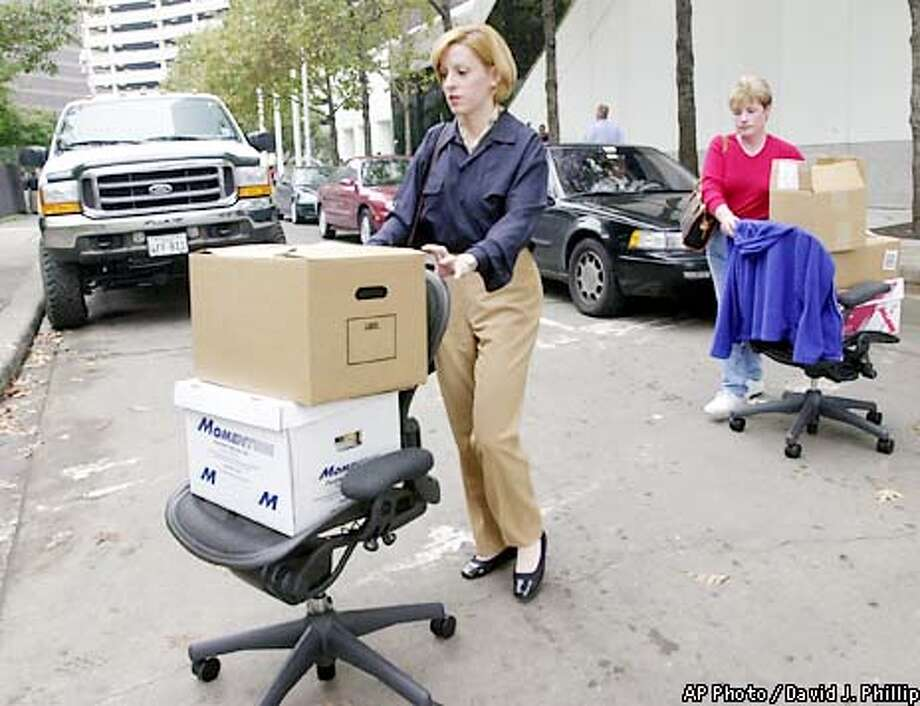 Laid-off Enron employees wheel some of their belongings across the street from company headquarters Monday, Dec. 3, 2001, in Houston. Enron filed for Chapter 11 protection and sued rival Dynegy Inc. for $10 billion as it tries to reverse a tailspin that has crippled the one-time energy giant. In the meantime, the company said an undetermined number of its 21,000 workers, mostly among the 7,500 in Houston, would be laid off. (AP Photo/David J. Phillip) Photo: DAVID J. PHILLIP