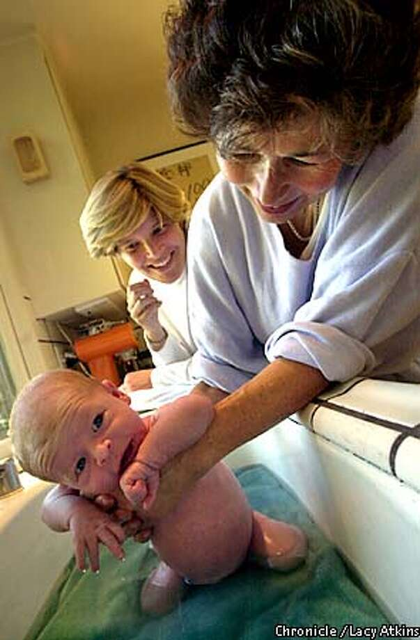 Doula, Vivian Sonnenberg shows mother Marian Baldauf how to give her new son Fritz, 3 weeks old a bath in the kitchen sink, Tuesday Oct.23, in San Francisco. Vivian, who has been a doula for 12 years and now works 50 hours a week for the Baldauf.  Photo By Lacy Atkins/SanFrancisco Chronicle Photo: Lacy Atkins