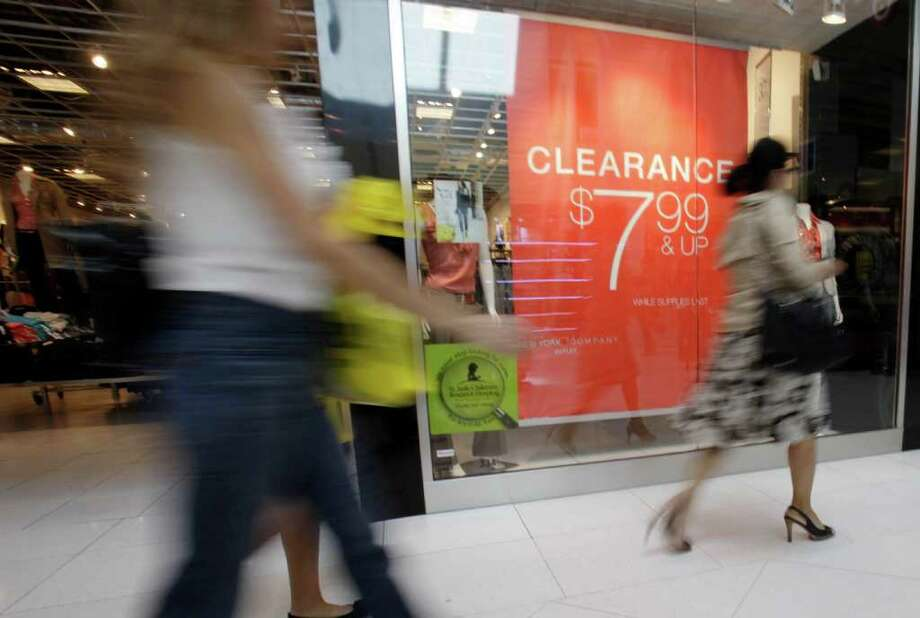 In this Nov. 9, 2011 file photo, shoppers walk past a clearance sign at the New York & Company outlet store at the Dolphin Mall, in Miami. Consumer spending was flat in December while incomes rose by the largest amount in nine months. But even with the December income surge, incomes for the whole year were up just half the amount of 2010, underscoring the challenge facing the economy. (AP Photo/Lynne Sladky, File) Photo: Lynne Sladky