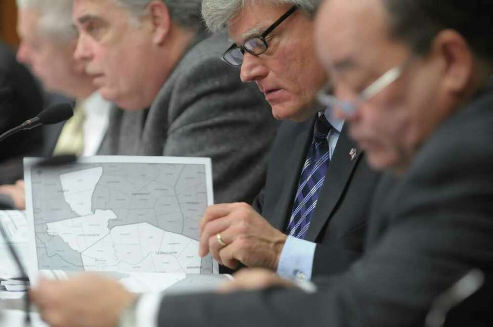 Senator Michael Nozzolio, center, looks over maps in a book of the proposed legislative districts during a public hearing held by members of the New York State Legislative Task Force on Demographic Research and Reapportionment at the Legislative Office Building on Monday, Jan. 30, 2012 in Albany, NY. Senator Nozzolio is co-chair of the task force, along with Assemblyman Jack McEneny, left. (Paul Buckowski / Times Union)