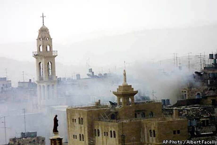 Smoke billows over the West Bank town of Bethlehem and the Church of the Nativity, left, Tuesday, April 2, 2002. Scores of Palestinian gunmen are hiding inside one of Christianity's holiest shrines, Bethlehem's Church of the Nativity, seeking refuge from Israeli troops that invaded the city as part of an offensive aimed at crushing Palestinian militias in the West Bank. (AP Photo/Albert Facelly) MAGAZINES OUT Photo: ALBERT FACELLY