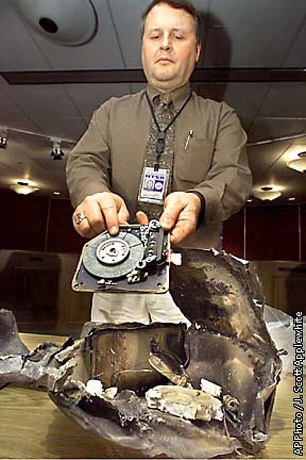 The charred casing of the flight voice recorder recovered from the crash of American Airlines flight 587 is displayed at the National Transportation Safety Board in Washington, Wednesday, Nov. 14, 2001. NTSB's Chief of Vehicle Recorder Division James Cash holds the tape assembly of the unit manufactured by Fairchild Aviation Recorders. The voice recorder was found at the crash site in the New York City borough of Queens. (  AP Photo / J. Scott Applewhite Photo: J. SCOTT APPLEWHITE