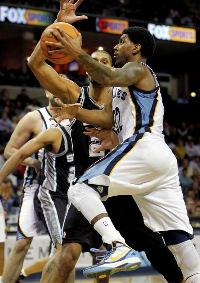 Memphis Grizzlies guard O.J. Mayo (32) drives past San Antonio Spurs forward Tim Duncan (21) for a shot in the second half of an NBA basketball game on Monday, Jan. 30, 2012, in Memphis, Tenn. The Spurs won 83-73. (AP Photo/Jim Weber) Photo: Associated Press