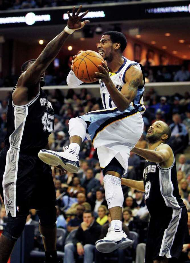 Memphis Grizzlies guard Mike Conley (11) looks to pass around San Antonio Spurs center DeJuan Blair (45) and guard Tony Parker (9), of France, in the first half of an NBA basketball game on Monday, Jan. 30, 2012, in Memphis, Tenn. (AP Photo/Jim Weber) Photo: Associated Press